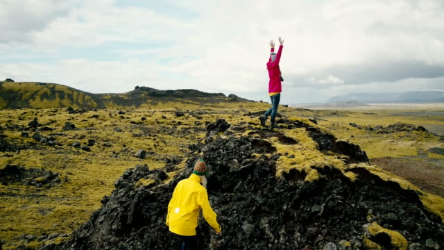 Aerial view of the group of tourists hiking on lava field in Iceland. Two woman raise hands up, feel happy and freedom video