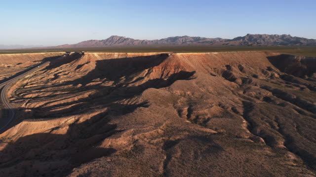 luftaufnahme der autobahn zwischen tafelbergen in einem hochland in der nähe von mesquite, nevada, usa, im frühen frühling. leichter verkehr von autos und lastwagen. drone 4k uhd video mit dem komplexen vorwärts und aufsteigend, am ende auch kippbare k - aerial overview soil stock-videos und b-roll-filmmaterial