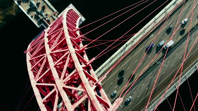 aerial view of the iconic landmark that is picturesque bridge which crosses the moscow river in moscow. cars traffic on cable-stayed bridge of red color at day time. 4k. - rzeka moskwa filmów i materiałów b-roll