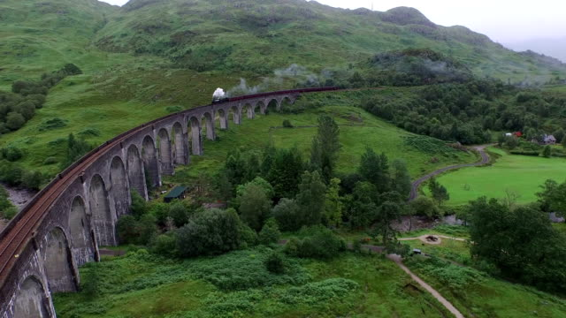 aerial view of the jacobite crossing glenfinnan viaduct - highlands scozzesi video stock e b–roll