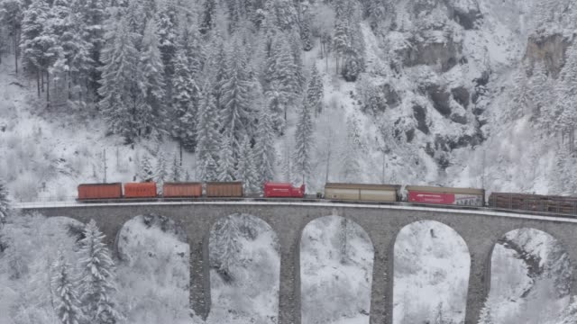 aerial view of the landwasser viaduct with cargo train of red color at winter, landmark of switzerland, snowing, drone turns after train - швейцарские альпы стоковые видео и кадры b-roll
