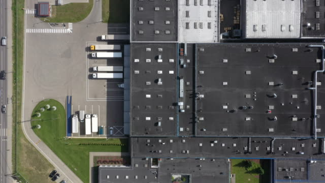 aerial view of the logistics warehouse with trucks waiting for loading - warehouse aerial stock videos & royalty-free footage