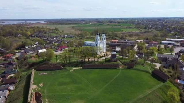 aerial view of the ludza medieval castle ruins on a hill between big ludza lake and small ludza lake and the roman catholic church in the background. - латвия стоковые видео и кадры b-roll