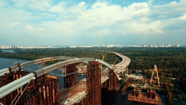 Aerial View of the Massive Bridge Over the River in Linking the Two Shores. the Road is Under Construction, Shot in 4K UHD video