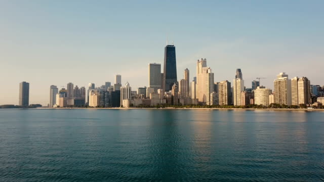 Aerial view of the Michigan lake and Chicago, America. Drone flying low over the water to the downtown in the morning Aerial view of the Michigan lake and Chicago, America. Drone flying low over the water to the downtown in the morning. Beautiful landscape of the skyscrapers in down. chicago architecture stock videos & royalty-free footage