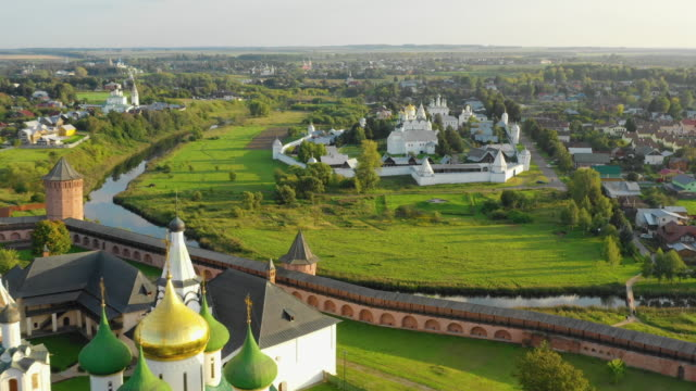 Aerial view of the Monastery of Saint Euthymius Suzdal, Russia. Aerial view of the Monastery of Saint Euthymius, Golden domes of the Cathedral, Kamenka river and Holy Intercession Convent russian culture stock videos & royalty-free footage