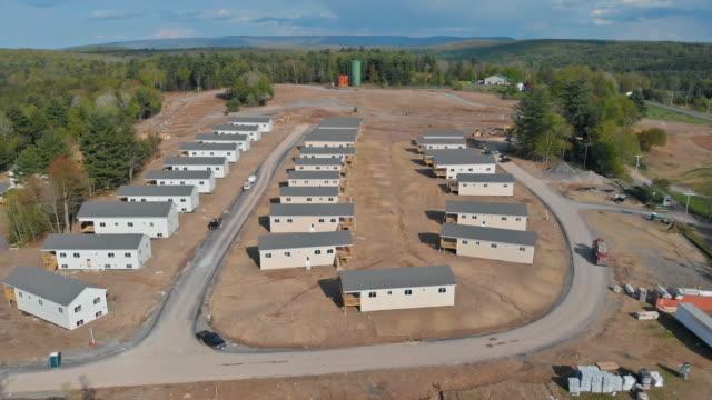 vídeos de stock e filmes b-roll de aerial view of the new home construction framing of mountain range summer landscape and a blue cloudy sky. - obras em casa janelas