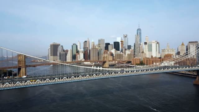 Aerial view of the New York, America. Drone flying under the Manhattan bridge to Brooklyn bridge through the East river Aerial view of the New York, America. Drone flying under the Manhattan bridge to Brooklyn bridge through the East river. Beautiful landscape of the famous sights in USA. manhattan bridge stock videos & royalty-free footage
