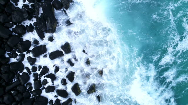aerial view of the ocean waves hitting against the rocks - pietra roccia video stock e b–roll