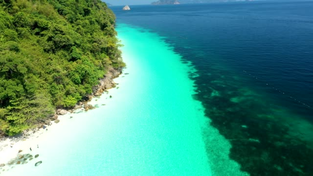 Aerial view of the ocean waves, white beaches and clear blue water and beautiful reefs and forests. Nyaung Oo Phee Island Myanmar video