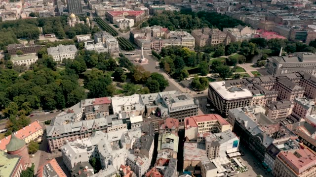 RIGA, LATVIA - MAY, 2019: Aerial view of the old Riga's roofs, city park and Brivibas square with monument of freedom.