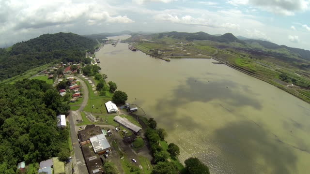 Aerial View of The Panama Canal, is a 77.1-kilometre (48 mi) ship canal in Panama that connects the Atlantic Ocean (via the Caribbean Sea) to the Pacific Ocean video