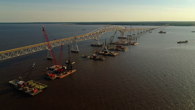 """Aerial view of the reconstruction of the Potomac River, near Governor Harry W. Nice Memorial/Senator Thomas """"Mac"""" Middleton Bridge connected Virginia and Maryland, with multiple floating cranes vessels along with the construction site on the water."""