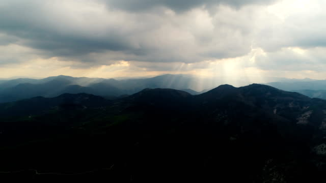 Aerial view of the Rhodopi mountains with sunbeams passing through the clouds video