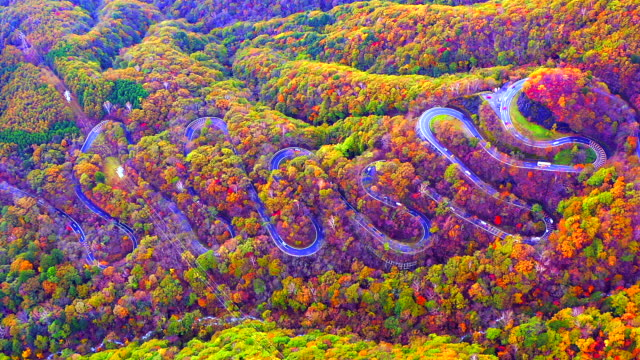 Aerial view of the road that curves back and forth in the mountains in the autumn of Japan