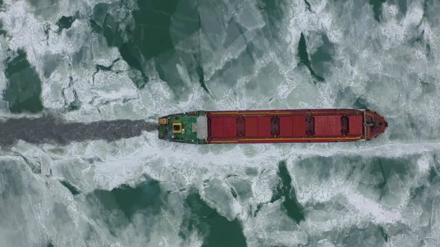 vídeos de stock e filmes b-roll de aerial view of the ship slowly moving through ice floes - gelo
