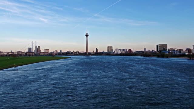 blick auf die skyline von düsseldorf während des fluges tief und schnell über den fluss rhein - deutschland - europa - düsseldorf stock-videos und b-roll-filmmaterial