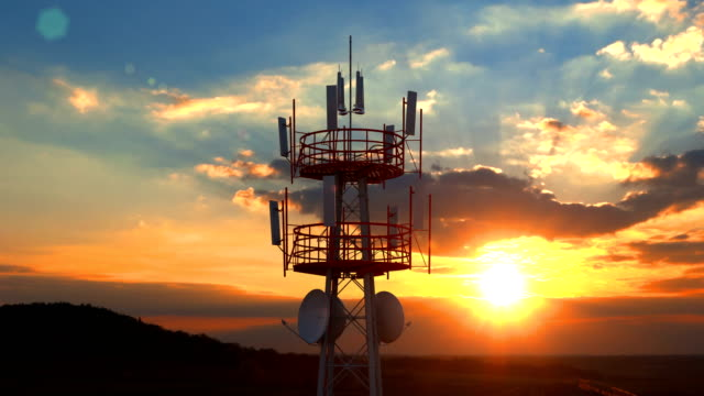 Aerial view of the top of telecommunication tower against scenic sunset Aerial view of the top of telecommunication tower. Its antennas designed for transmitting cellular mobile signals covering large areas providing high speed 4g and modern 5g traffic network service. electrical equipment stock videos & royalty-free footage