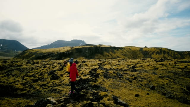 Aerial view of the tourists walking on the lava field in Iceland. Two woman hiking on the mountain, enjoying the hobby video