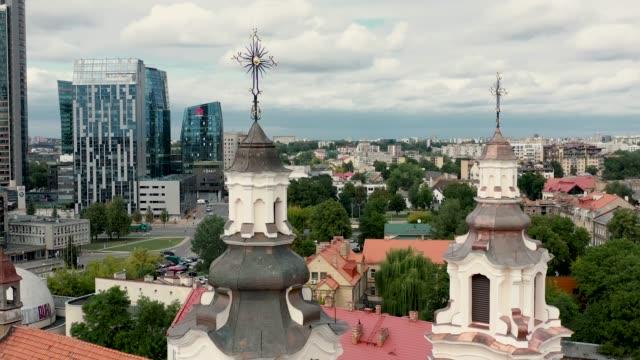 vilnius, lithuania - juli 2019: luftaufnahme der türme der kirche des erzengels raphhael und des geschäftszentrums vilnius. - litauen stock-videos und b-roll-filmmaterial