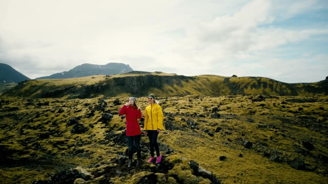 Aerial view of the two woman in the lava field in Iceland raise hands. Happy tourists send air kiss to copter video
