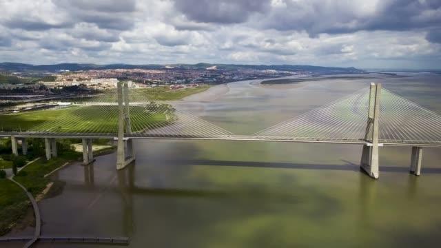 Aerial view of the Vasco da Gama bridge in Lisbon, Portugal. Top view of the longest bridge in Europe Aerial view of the Vasco da Gama bridge in Lisbon, Portugal. Top view of the longest bridge in Europe. suspension bridge stock videos & royalty-free footage