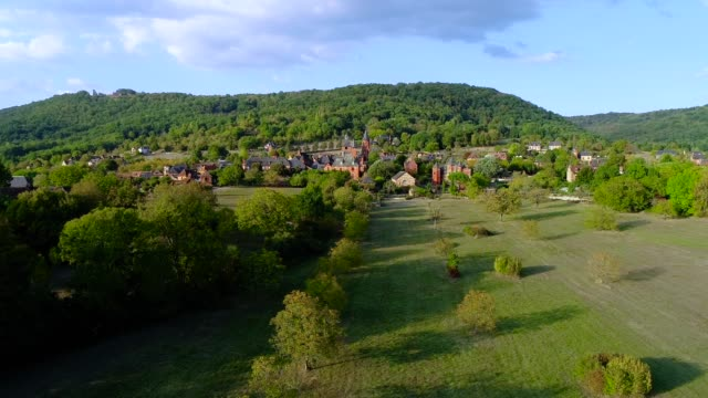 Aerial view of the village of Collonges-La-Rouge in France. The village is in the middle of a forest and green fields.