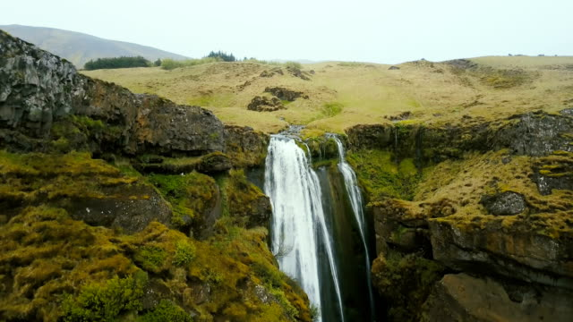 Aerial view of the waterfall Gljufrabui in Iceland. Copter flying over the green valley and river falling down video