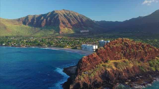 Aerial view of the west coast of Oahu island Aerial view of the west coast of Oahu island during sunrise, orbiting flight over the coastline with Makaha valley and its beaches oahu stock videos & royalty-free footage