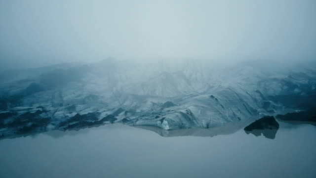 Aerial view of the white glacier Myrdalsjokull with black ash in Iceland. Eternal ice in fog in mountain video