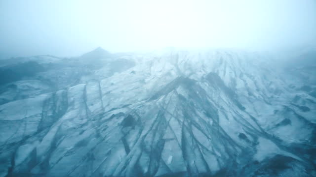 Aerial view of the white glacier Myrdalsjokull with black ash in Iceland. Copter flying over the iceberg in the fog video
