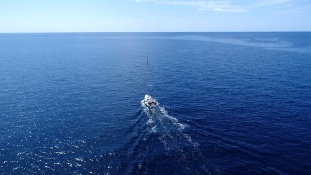 Aerial view of the white yacht running on the blue sea in Montenegro Aerial view of the white yacht running on the blue sea in Montenegro recreational boat stock videos & royalty-free footage