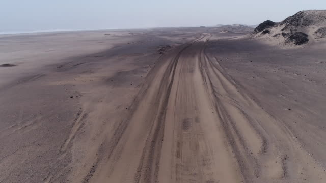 4K aerial view of the windswept sand road that runs along the shoreline of the Skeleton Coast, Namibia