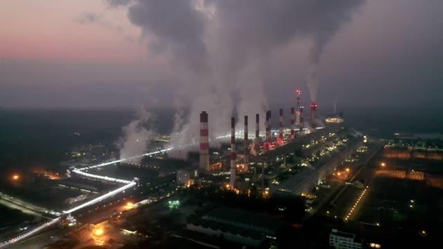 vidéos et rushes de vue aérienne de centrale thermique ou centrale de charbon et tour de refroidissement avec la vapeur la nuit au jour - usine