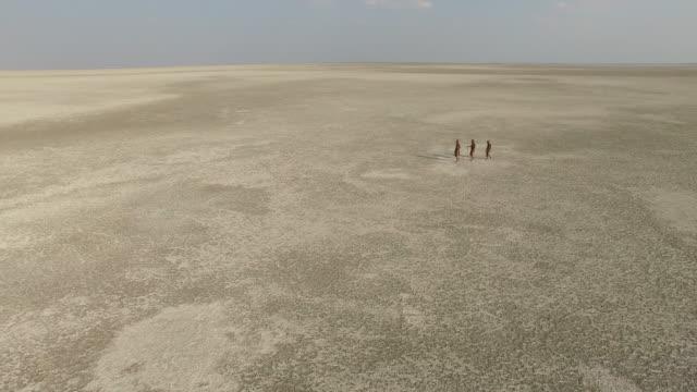 Aerial view of three Bushmen walking over the vast expanse of the Makgadikgadi Pans, Botswana Aerial view of three Bushmen walking over the vast expanse of the Makgadikgadi Pans, Botswana makgadikgadi pans national park stock videos & royalty-free footage