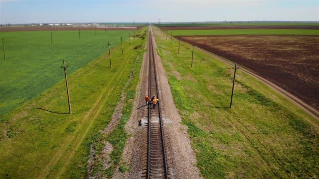 Flygfoto över tre järnvägsarbetare bär vagn längs räls för att utforska spår och förhindra olyckor video