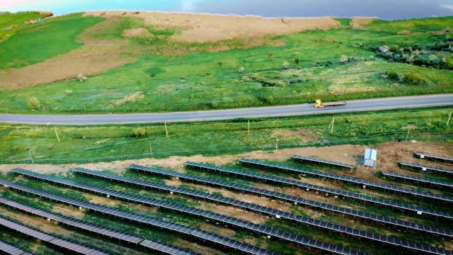 Flygbild av tre last bilar med släpvagn gå på motorväg nära sol kraftverk ligger i fält nära älven med tjocka vass video