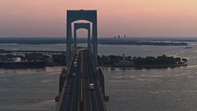 Aerial view of Throgs Neck Bridge over East River connecting Queens and Bronx Boroughs, New York, at sunrise. Drone video footage with the panoramic camera motion