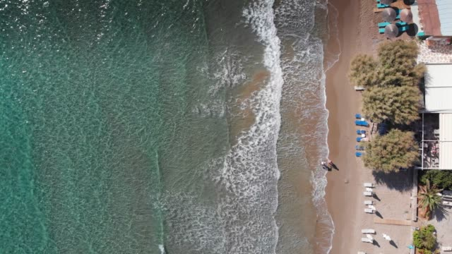 Aerial view of tourists with deck chairs and beach umbrellas at the coast of Greek Island, Crete, Greece