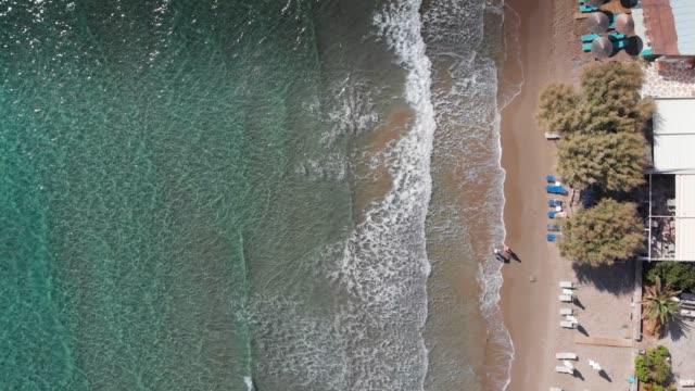 Luftaufnahme von Touristen mit Liegestühlen und Sonnenschirmen an der Küste der griechischen Insel, Kreta, Griechenland – Video
