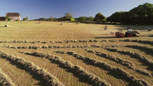 vidéos et rushes de vue aérienne du tracteur récolte des ballots de paille. - foin