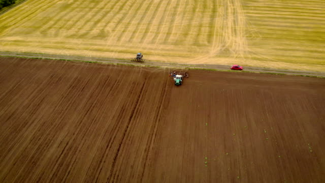 aerial view of tractor with seeder makes u-turn and goes into field to sow seeds - orzo video stock e b–roll