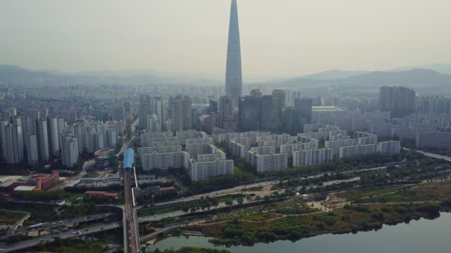 Aerial view of traffic of car driving on bridge cross over Han river into Lotte World Tower in Seoul city, South Korea Aerial view of traffic of car driving on bridge cross over Han river into Lotte World Tower in Seoul city, South Korea south korea stock videos & royalty-free footage