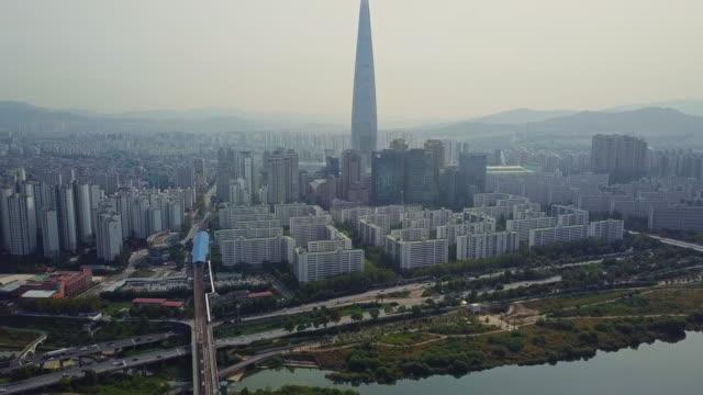 seul şehrinde lotte dünya kulesi içine han nehri üzerinde köprü çapraz araba sürüş trafik havadan görünümü, güney kore - güney kore stok videoları ve detay görüntü çekimi