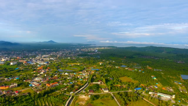 aerial view of tranquil coastal village with tropical mountain background - графство дерри стоковые видео и кадры b-roll