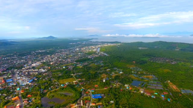aerial view of tranquil coastal village with tropical mountain background with morning sunlight - графство дерри стоковые видео и кадры b-roll