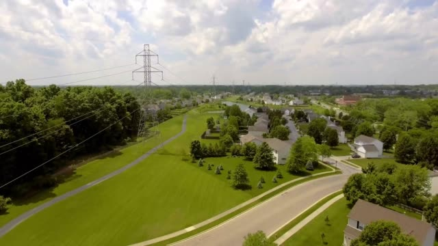 Aerial View of Transmission Towers and Wires Near Suburban Neighborhood