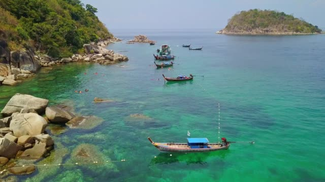 Aerial view of tropical beach, long tail boat, kayak and rocky coast with crystal clear turquoise water Koh Lipe, Satun, Thailand Bird's eye view of tropical beach, long tail boat, kayak and rocky coast with crystal clear turquoise water Koh Kla, Koh Lipe, Satun, Thailand pattaya stock videos & royalty-free footage