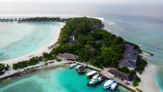 Aerial view of tropical island resort hotel with white sand palm trees and turquoise Indian ocean on Maldives, dock, boats and ferries drone footage from above in 4k video