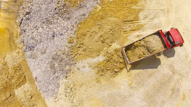 Aerial view of truck riding on muddy road trough a construction site. Aerial view of truck riding on muddy road trough a construction site. Heavy industry from above. Industrial footage from devastated landscape. dump truck stock videos & royalty-free footage